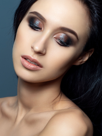 Portrait of beautiful brunette woman with evening makeup. Shiny multicolor smokey eyes. Luxury skincare and modern fashion makeup concept. Studio shot. Stockfoto