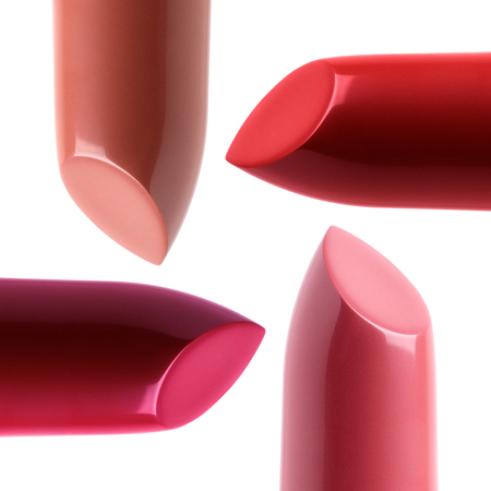Closeup view of four different colored lipsticks on white background. Makeup, cosmetics and drugstore concept