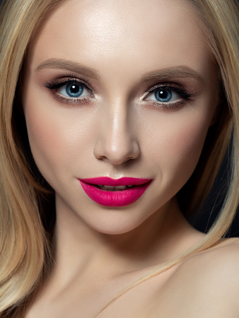 Portrait of beautiful blonde woman with bright makeup. Golden smokey eyes and pink lips. Luxury skincare and modern fashion makeup concept. Studio shot.
