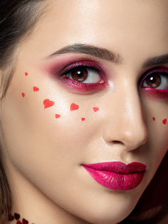 Portrait of young beautiful woman with fashion make up with little hearts on her cheek. Modern bright pink lips and smokey eyes. Studio shot. Valentines day concept