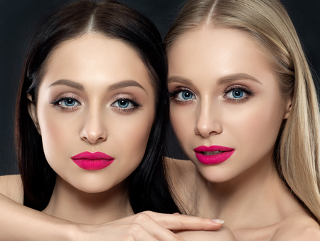 Closeup portrait of two young beautiful women over black background. Bright pink lipstick. Skin care, cosmetics, SPA therapy or cosmetology concept Stockfoto