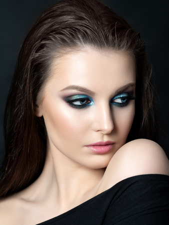 Portrait of beautiful woman with fashion makeup. Modern blue smokey eyes make up. Studio shot