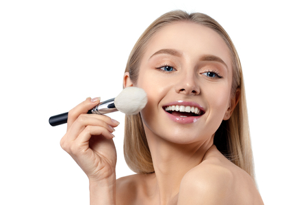 Young beautiful caucasian woman applying makeup. Smiling woman with powder brush isolated over white background