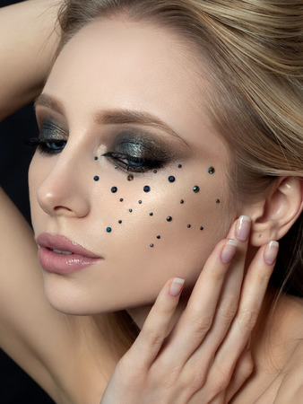 Close up beauty portrait of young woman with beautiful fashion makeup touching her face. Modern fashion makeup. Long lashes, bronze smokey eyes, black rhinestones. Studio shot. Stockfoto