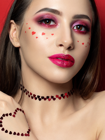 Portrait of young beautiful woman with fashion make up with little hearts on her cheek. Modern bright pink lips and smokey eyes. Studio shot. Valentines day concept. Copy space Stockfoto