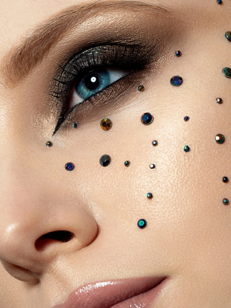 Close up beauty portrait of young woman with beautiful fashion makeup. Modern fashion makeup. Long lashes, bronze smokey eyes, black rhinestones. Studio shot. Extreme closeup, partial face view Stockfoto