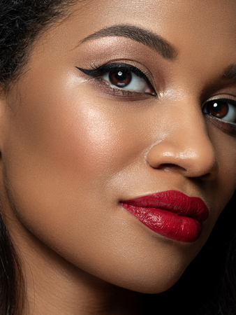 Portrait of young beautiful african woman with evening make up. Red lips, golden eyeshades and black eyeliner. Classic makeup concept. Studio shot. Extreme closeup, partial face view Stockfoto - 117645782