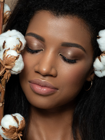 Portrait of young beautiful black woman with cotton flowers. Cleaning skin, SPA therapy, skincare and cosmetology concept