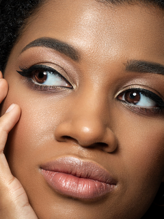 Closeup portrait of young beautiful black woman touching her face. Cleaning skin, SPA therapy, skincare, cosmetology and plastic surgery concept