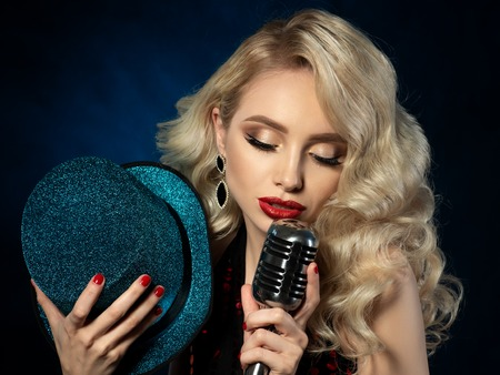 Portrait of pretty blond female singer holding microphone Stockfoto