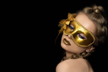 Young beautiful woman wearing golden party mask Stockfoto