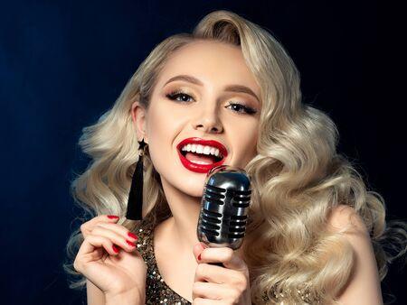 Portrait of pretty blond female singer holding microphone 写真素材