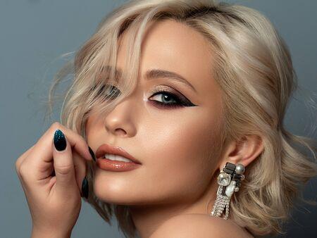 Porträt der jungen schönen blonden Frau mit Abend bilden das Berühren ihres Kopfes. Moderner Mode-Eyeliner-Flügel und schöner Ohrring. Studioaufnahme.