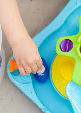 Child's hand playing with water game, car, star, boat Stock Photo - 137060736