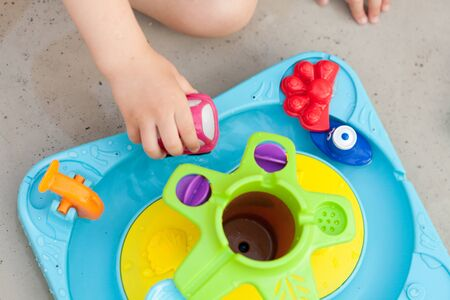Child's hand playing with water game, car, star, boat Stock Photo - 137060747