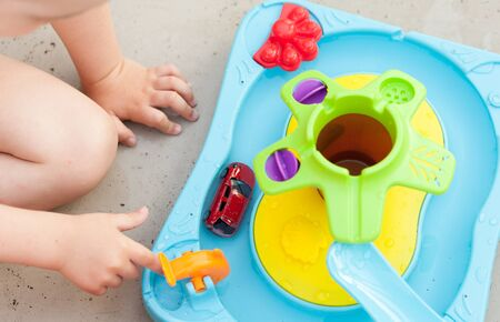 Childs hand playing with water game, car, star, boat Stock Photo