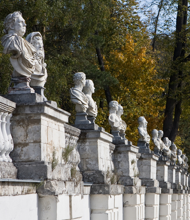 old white wall with antique statues against a background of autumnal trees