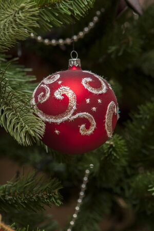 Closeup of red bauble hanging from a decorated Christmas tree Reklamní fotografie