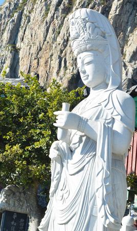quan yin buddha scupture make by white stone mountain background photo