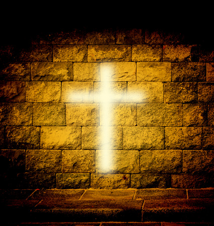 Christian religious cross with gold light on the brick wall Stockfoto