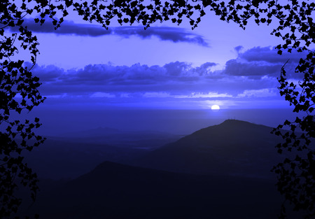Beautiful sunset with cloud and mountain,tree foreground siluette frame,blue color tone photo
