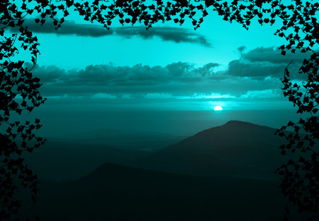 Beautiful sunset with cloud and mountain,tree foreground siluette frame,cyan color tone photo