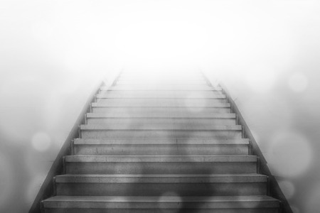 stairway: stairway going up to white light with bokeh light background,gray color tone Stock Photo