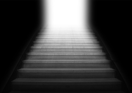 Staircase going up to the white light from the dark area,gray color monotone photo
