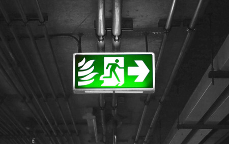 fire exit sign: Fire exit sign in car park building gray