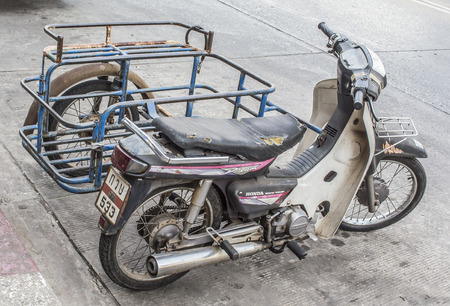 indigent: old sidecar motorcycle park on the road in udonthani,thailand
