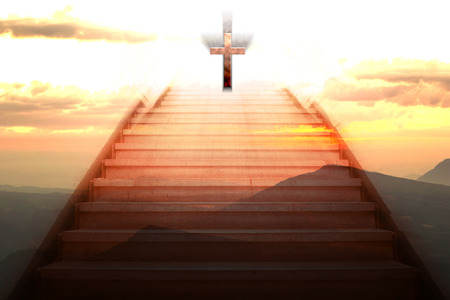 staircase going up to the christian cross with mountain background photo