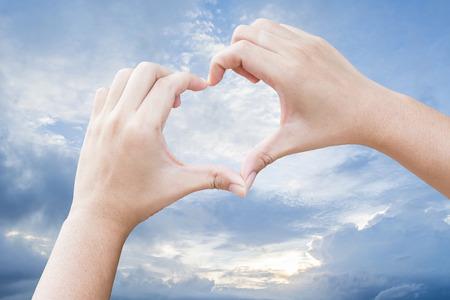 Handen in de vorm van hart met hemelachtergrond Stockfoto