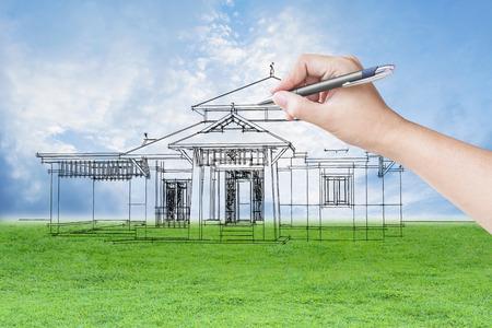 architect hand tekenen van een huis op het gebied gras en hemel achtergrond Stockfoto