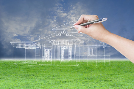 architect drawing: architect hand drawing a house on the grass field and sky background