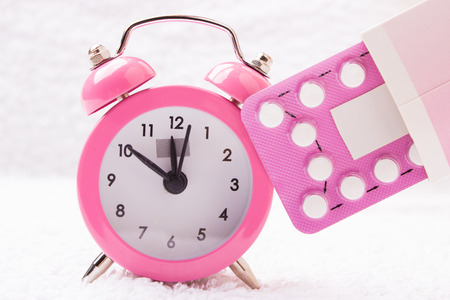medicine and birth control. alarm clock and contraceptive pills Stockfoto