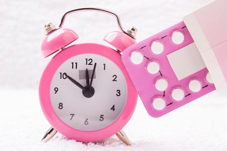 nacimiento: medicina y control de la natalidad. despertador y píldoras anticonceptivas Foto de archivo