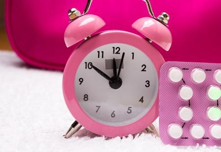 birth prevention: medicine and birth control. alarm clock and contraceptive pills Stock Photo