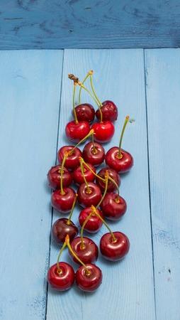 rustical: fresh cherries on a blue board closeup