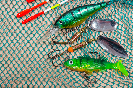wobbler: bait, wobbler and fishing accessories on a fishing net background