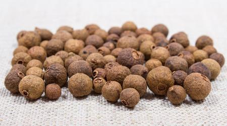 allspice: Grains of allspice on canvas background closeup Stock Photo