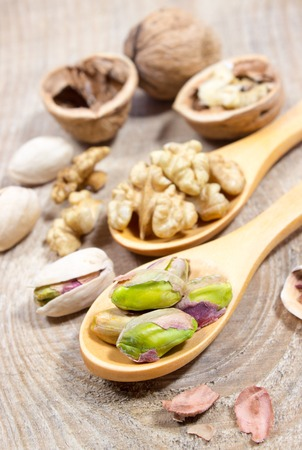 pistachios: Closeup of a walnut and pistachios on wooden background. Stock Photo