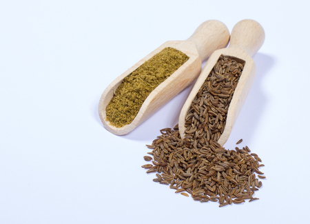 cumin: Ground cumin in a spoon and whole cumin isolated on white background. Stock Photo