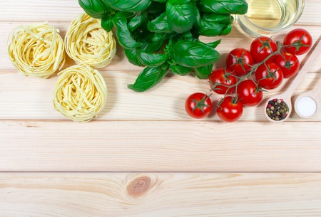aceite de cocina: Raw homemade pasta and ingredients for pasta on wooden background.