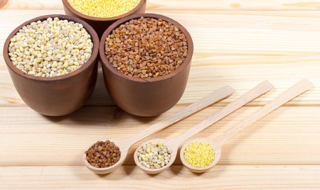 pearl barley: Pearl barley, buckwheat and millet groats on wooden background.