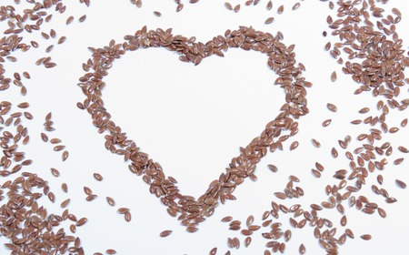 flaxseed on white background with a wooden spoon 写真素材