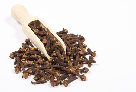 Closeup of dried cloves on a white background.
