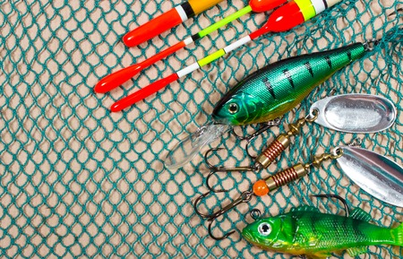net fishing: bait, wobbler and fishing accessories on a fishing net background