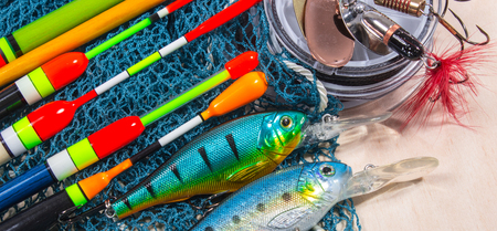 fish hook: bait, wobbler and fishing accessories on wooden background Stock Photo