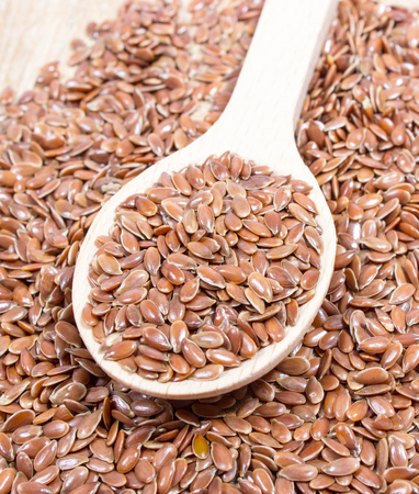 flaxseed: flaxseed on wood background with a wooden spoon
