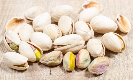 nutshells: Closeup of pistachio nuts on wood background Stock Photo